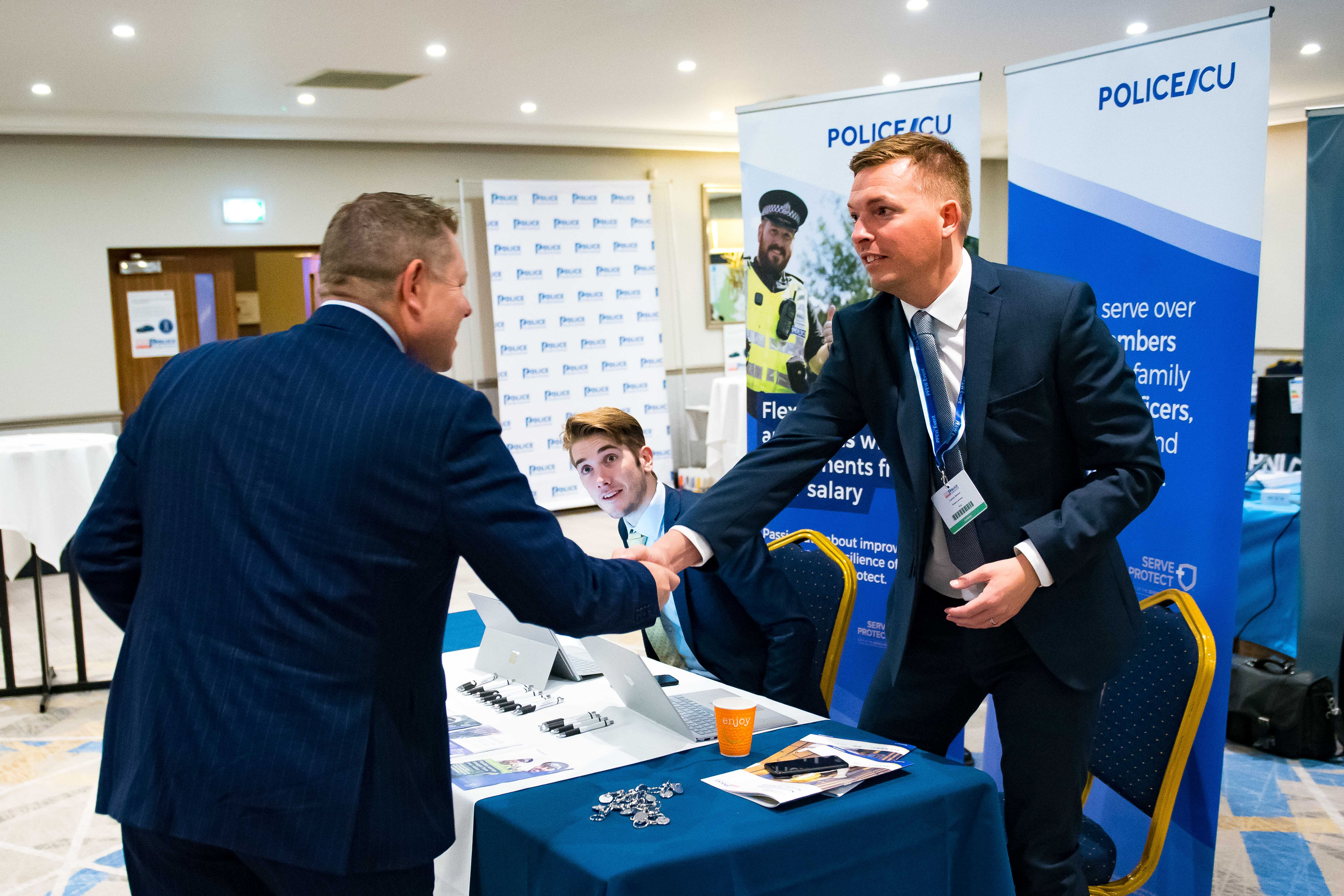 PFEW Chair John Apter (left) greets an exhibitor at the Custody Seminar, one of several events put on by PFEW this year